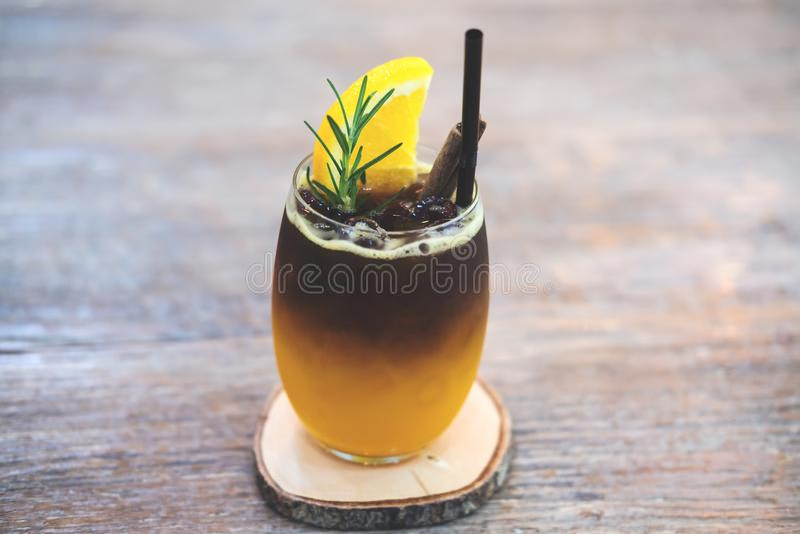 Nahaufnahmebild eines Glases orange kalten Gebräukaffees auf Holztisch lizenzfreie stockfotografie