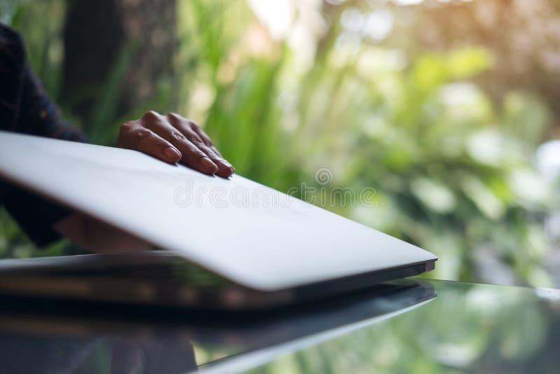 Nahaufnahmebild von ein Geschäftsfrau ` s Händen schließen und öffnen Laptop auf Glastisch im Büro mit Unschärfegrünnatur stockfoto