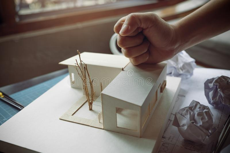 Nahaufnahmebild von verärgerte Architekten versuchen, ein Architekturmodell auf dem Tisch zu zerstören stockfoto