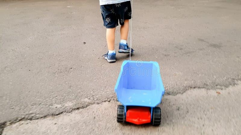 Nahaufnahmebild wenigen Jungen, der auf Straße geht und großen Spielzeuglastwagen durch Seil zieht stockbild