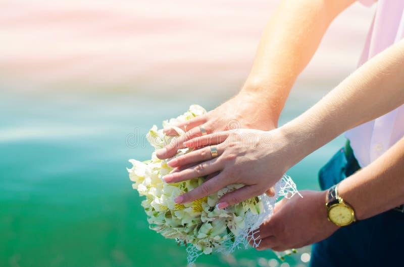 Nahaufnahmebraut und -bräutigam ` s Hände mit Eheringen und Blumenstrauß Liebe und Verbindung Hochzeitszubehör und -dekor auf dem stockfotos