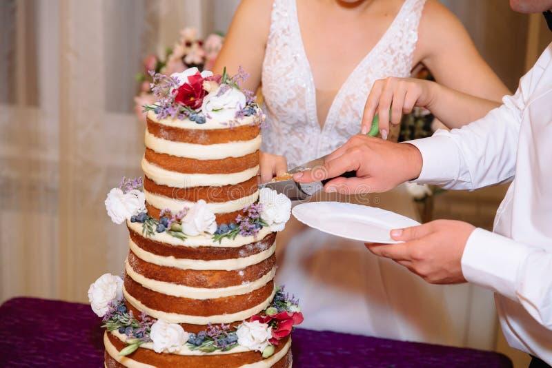 Nahaufnahmebraut- und -bräutigamhände schnitten die mehrstufige weiße Hochzeitstorte, die mit Blumenständen auf einer Tabelle ver lizenzfreie stockbilder