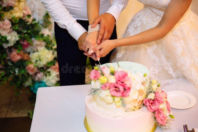 Nahaufnahmebraut- und -bräutigamhände schnitten die mehrstufige weiße Hochzeitstorte, die mit Blumenständen auf einer Tabelle ver stockfotos