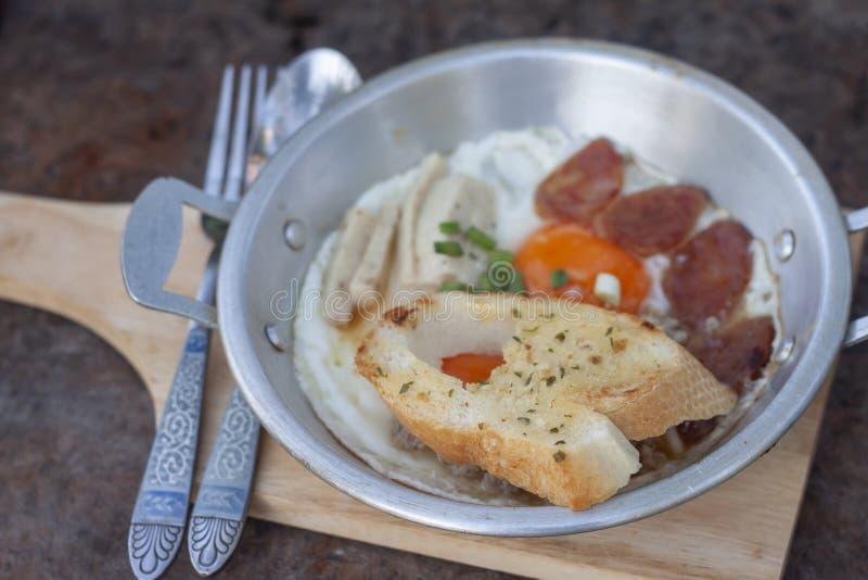 Nahaufnahmebrot in Pan-gebratenem Ei mit Belägen ist Frühstück lizenzfreie stockfotografie