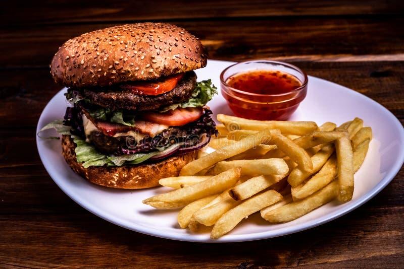Nahaufnahmeburger mit Rindfleischkotelett auf einem hölzernen Brett, dunkler Hintergrund der Nahaufnahme lizenzfreie stockfotos