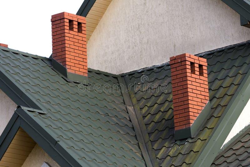 Nahaufnahmedetail der neuen modernen Hausspitze mit geschichtetem grünem Dach, hohen Ziegelstein-roten Kaminen und Stuckwänden Be lizenzfreies stockbild