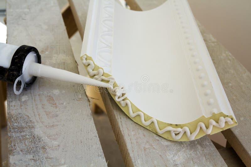 Nahaufnahmedetail des Dekorationsformteils mit Kleberkleber vor Installation in der Innenerneuerung lizenzfreie stockbilder