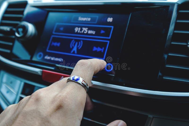 Nahaufnahmefinger-Pressedrehung die Musik, auf dem Touch Screen digital im Auto lizenzfreie stockfotografie