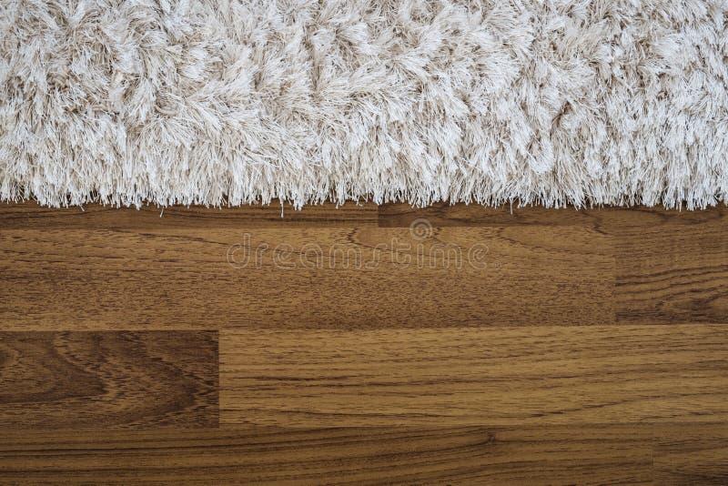 Nahaufnahmeflaumiger Luxusteppich auf lamellenförmig angeordnetem Holzfußboden stockfoto
