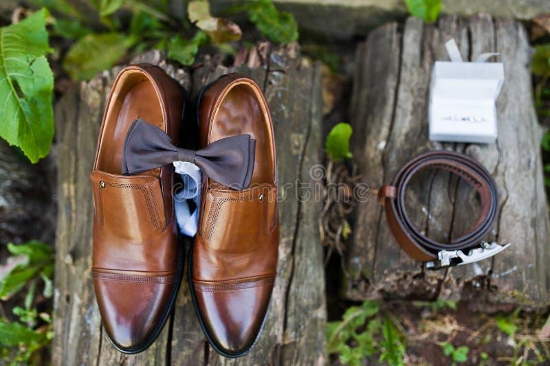 Nahaufnahmefoto Bräutigam ` s von Schuhen, von Manschettenknöpfen, von Gurt und von Fliege an stockbild