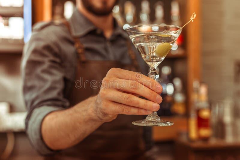 Nahaufnahmefoto der Bararbeitskraft ein Martini-Cocktail halten lizenzfreie stockbilder