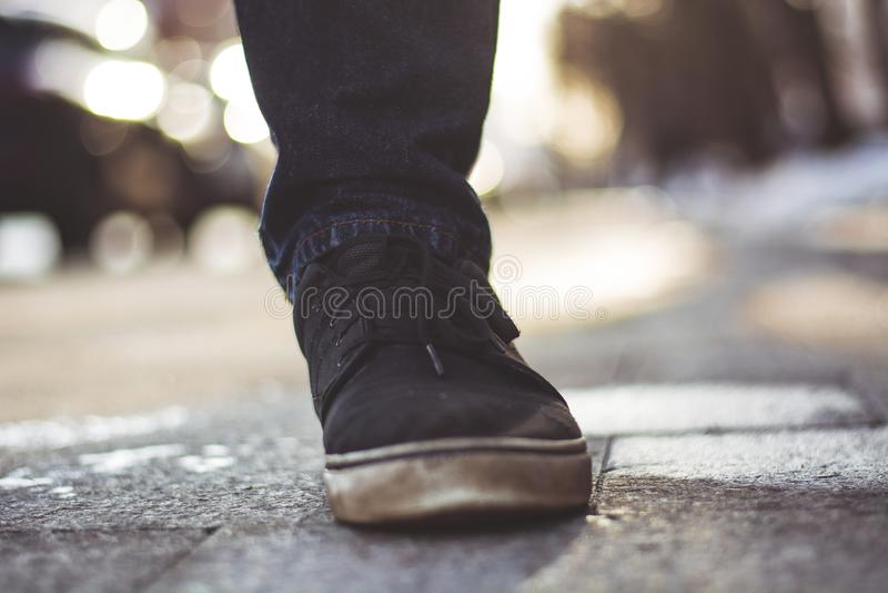 Nahaufnahmefoto der Beine der Männer in den schwarzen Turnschuhen stockfotos