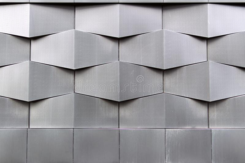 Nahaufnahmefoto der grauen modernen Gebäudefassade, geometrisches Muster der Architektur lizenzfreies stockbild