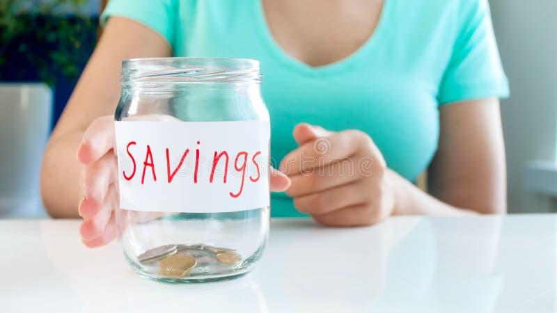 Nahaufnahmefoto der jungen Frau fast leeres Glasgefäß für Geldeinsparungen nehmend lizenzfreies stockbild