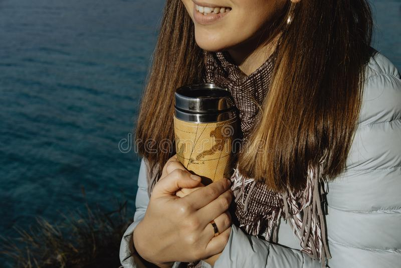 Nahaufnahmefoto der jungen Frau im blauen Mantel hält eine Thermosflasche mit h stockfoto