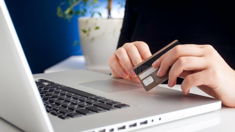 Nahaufnahmefoto der jungen Frau online auf Laptop in der Hand kaufen und Kreditkarte halten tuend stockfotos
