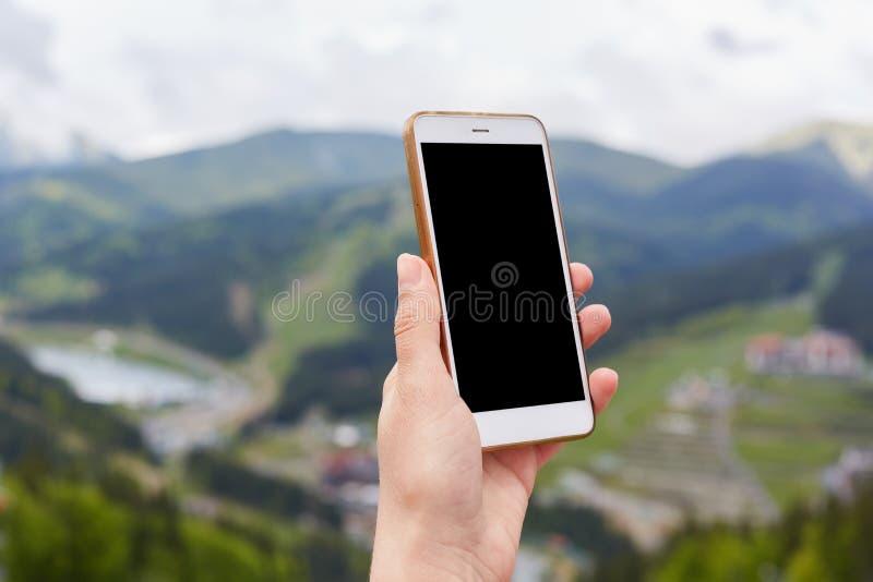Nahaufnahmefoto der unbekannten Handholding schaltete Smartphone mit leerem Bildschirm über dem Gebirgshintergrund und suchte nac stockfoto