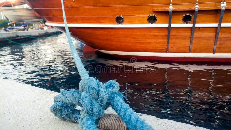 Nahaufnahmefoto des alten großen Seils, das historisches hölzernes Schiff am Hafen festmacht stockfotografie