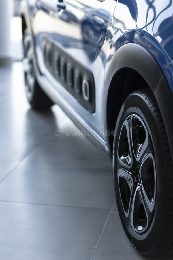 Nahaufnahmefoto des blauen glänzenden Autos mit den schwarzen Rädern, die im Autosaloninnenraum stehen stockbild