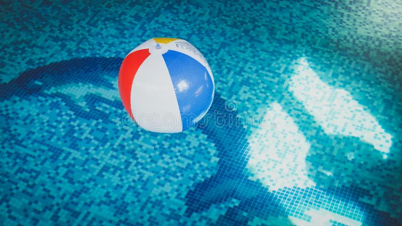Nahaufnahmefoto des bunten gestreiften aufblasbaren Wasserballs, der auf die Wasseroberfläche am Swimmingpool schwimmt stockbilder
