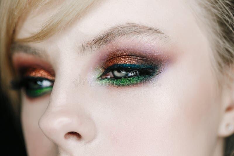 Nahaufnahmefoto des geöffneten Frauenauges mit den schönen hellen Make-up, Braunen und Grünenrauchigen Augen, die rechte Seite sc stockfotografie