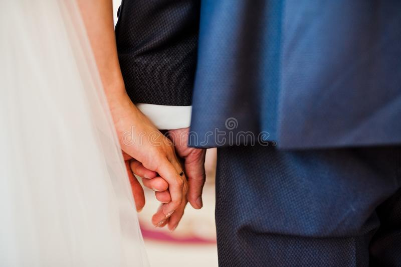 Nahaufnahmefoto des Hochzeitspaarhändchenhaltens stockfotografie