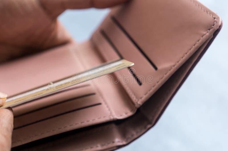Nahaufnahmefoto des jungen Geschäftsmannes setzend oder herausnehmend oder mit Kreditkarte in der ledernen Geldbörse auf weißem H lizenzfreie stockbilder