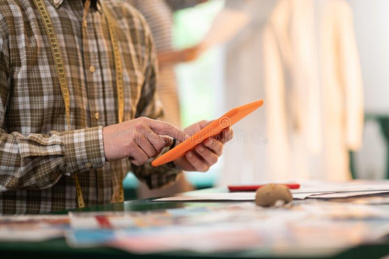 Nahaufnahmefoto des Mannes eine Tablette in den Händen halten lizenzfreie stockbilder