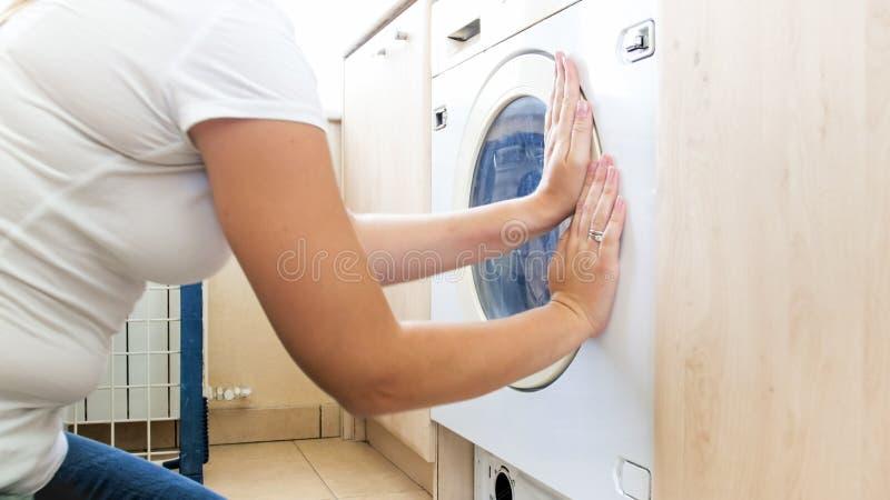 Nahaufnahmefoto junge Frau schließend dorr der Waschmaschine voll von schmutziger Kleidung lizenzfreie stockbilder