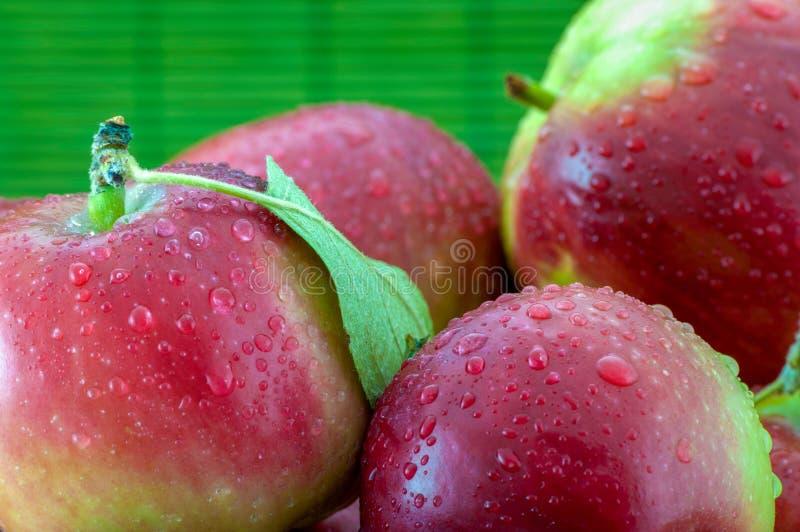 Nahaufnahmefoto von Äpfeln mit Wasser fällt auf unscharfen grünen Hintergrund lizenzfreies stockbild