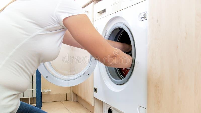 Nahaufnahmefoto von den weiblichen Händen, die Kleidung aus Waschmaschine heraus nehmen lizenzfreies stockbild