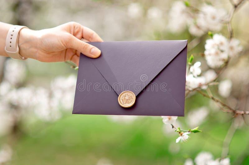 Nahaufnahmefoto von den weiblichen Händen, die purpurroten Einladungsumschlag mit Wachssiegel, Geschenkgutschein, Postkarte, Hoch lizenzfreie stockbilder