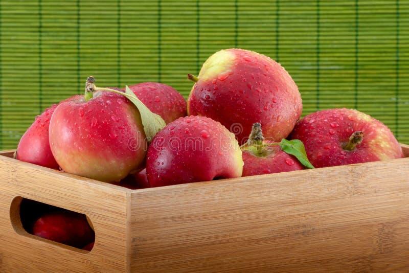 Nahaufnahmefoto von nassen Äpfeln in einer Bambuskiste auf grünem Hintergrund stockbilder