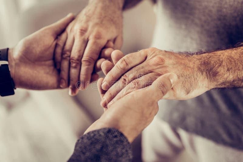 Nahaufnahmefoto von zwei männlichem Händchenhalten in den Händen lizenzfreie stockfotos