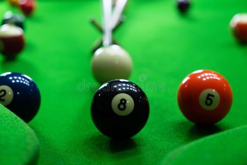 Nahaufnahmefotos, die Billardkugeln, verschiedene Zahlen spielend und erstechen den Ball, die Zahlen und den grünen Boden lizenzfreies stockbild