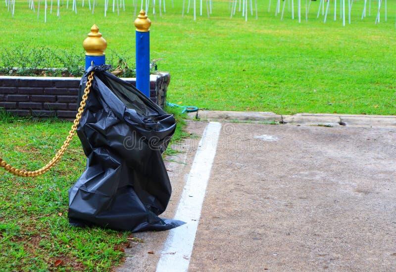 Nahaufnahmefotos von schwarzen Abfalltaschen für das Setzen des Abfalls auf den Hintergrund des grünen Grases lizenzfreies stockbild