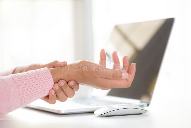 Nahaufnahmefrau, die ihre Handgelenkschmerz von der Anwendung des Computers hält büro stockbild