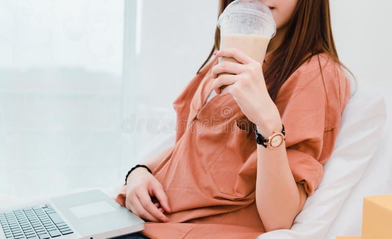 Nahaufnahmefrau, die kalten Kaffee trinkt und Laptop verwendet lizenzfreies stockfoto