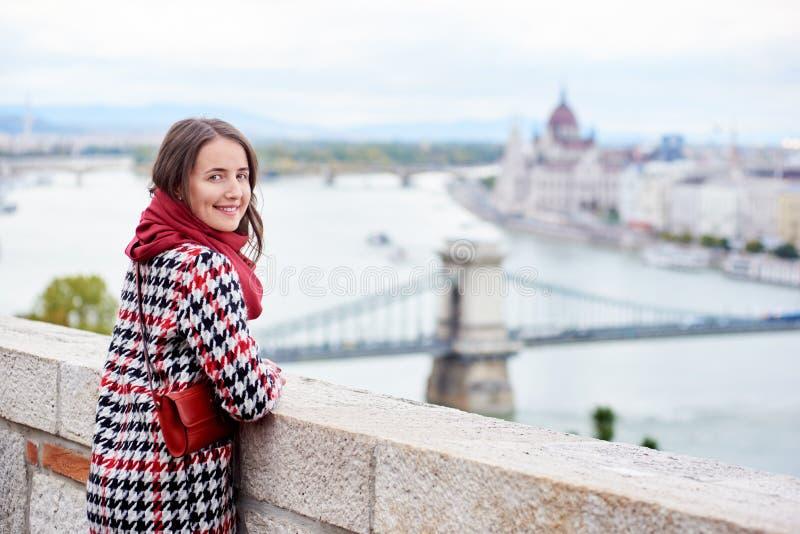 Nahaufnahmefrau, die zurück Kamera gegen das Ansicht Ungar-Parlament betrachtet lizenzfreies stockfoto