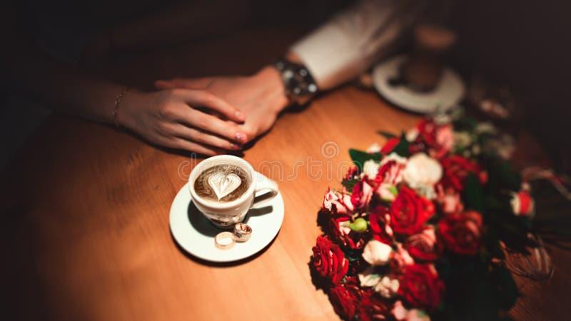 Nahaufnahmefrau ` s Hand mit Tasse Kaffee und goldenen Eheringen Brautblumenstrauß auf Hintergrund Romantisches Datum in lizenzfreie stockfotografie