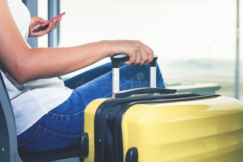 Nahaufnahmefrau trägt Ihr Gepäck am Flughafenabfertigungsgebäude lizenzfreie stockfotos