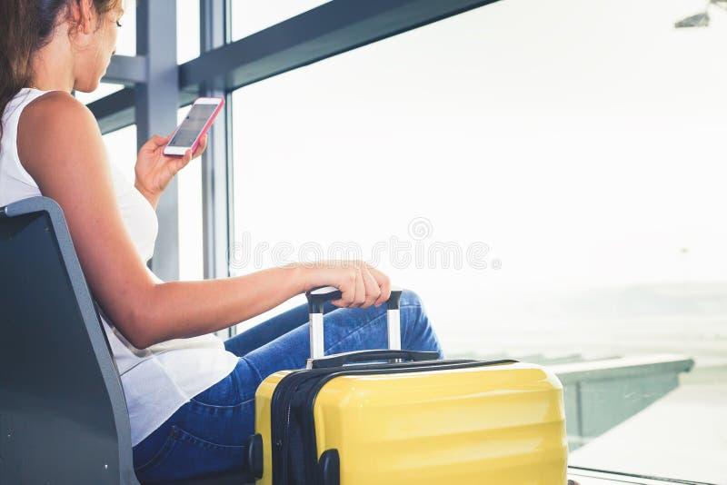 Nahaufnahmefrau trägt Ihr Gepäck am Flughafenabfertigungsgebäude stockfotografie