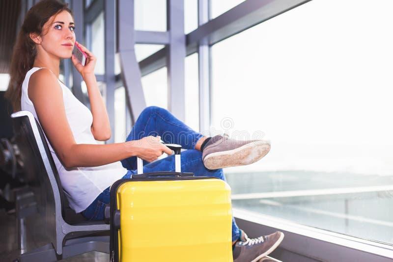 Nahaufnahmefrau trägt Ihr Gepäck am Flughafenabfertigungsgebäude stockbild