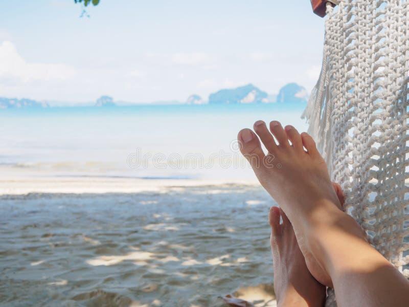 Nahaufnahmefrauenfüße, die auf Hängematte mit Bäumen und schönem Meer liegen stockfotos