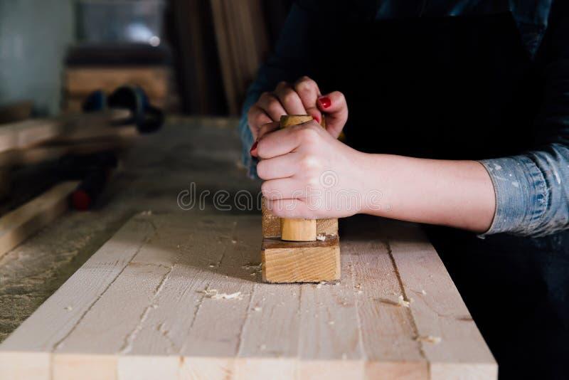 Nahaufnahmefrauenhände des Tischlers, der Fläche mit hölzerner Planke in der Zimmereiwerkstatt verwendet stockbild
