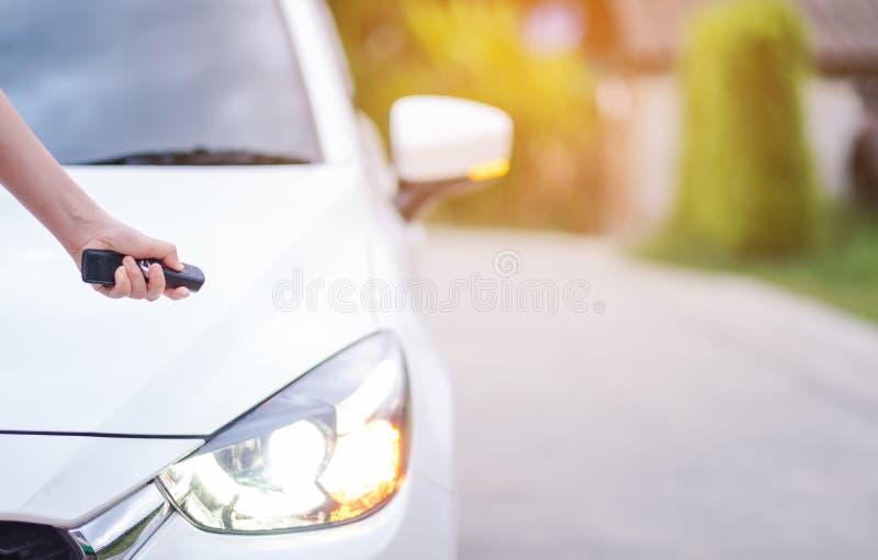 Nahaufnahmefrauenhand, welche die Fernsteuerungsautoalarmsysteme h?lt stockfotos
