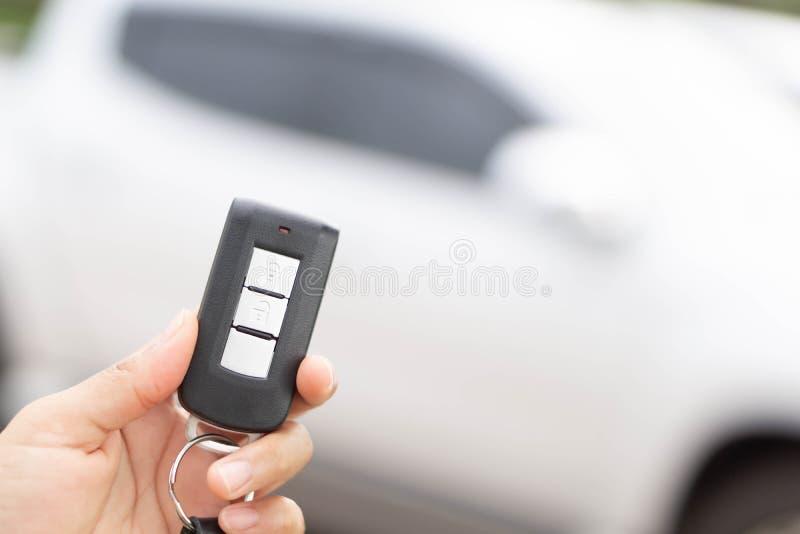 Nahaufnahmefrauenhandholding-Autoschlüssel entfernt mit Autohintergrund stockfotos