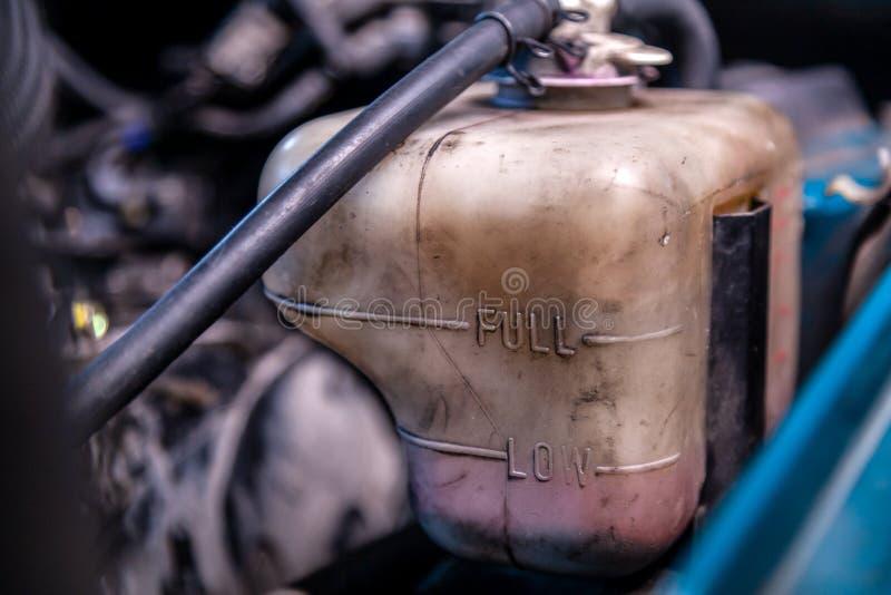 Nahaufnahmefrostschutzmittel-Expansionsbehälter unter der Haube des Autos stockfotografie