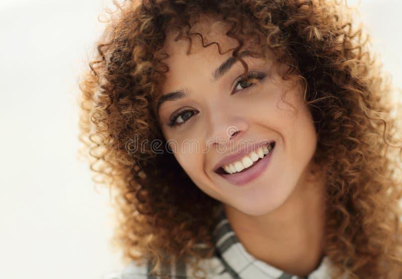 Nahaufnahmegesicht der schönen jungen Frau mit dem gelockten Haar lizenzfreie stockbilder