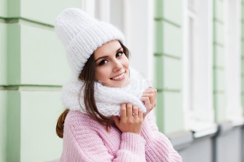 Nahaufnahmegesicht einer jungen lächelnden Frau, die den Winter gestrickten Schal und Hut tragend genießt stockbild